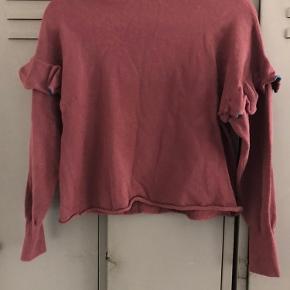 Rigtig fin retro tynd striksweater i støvet Bordeaux med fræser på begge ærmer med en blå stribe på flæsen. Brugt få gange og har ingen slitage eller skrammer.