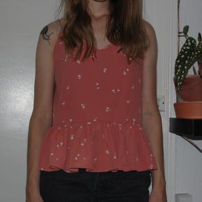 Rosa/lyserød sommertop med flot åben ryg og peplumskørt. Kan justeres ved hjælp af stropperne, som kan bindes i knuder. Sælges da jeg desværre aldrig får den brugt, på trods af at den er virkelig fin!
