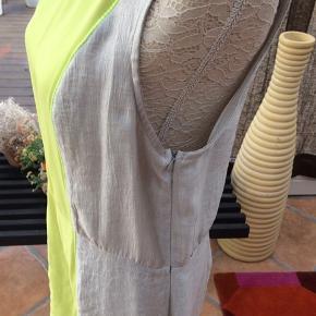 Kjolen er af mærket Millioner & Honey. Købt i Milano. Der er skjult lynlås i siden og kjolen krøller ikke😊. Farverne er grå/sølv og lime. Ny pris omregnet til kr 1300,-.
