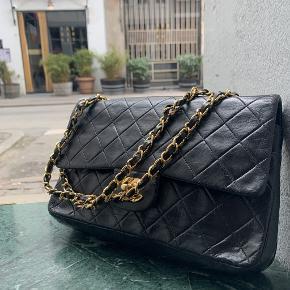 Ældre Chanel Flap bag i sort.  Tasken fremstår i flot velholdt stand, med små naturlige brugsspor. Tasken er blevet professionelt farvet for at vedligeholde standen.  Der medfølger ikke originalt købstilbehør til tasken.  Tasken måler ca 22x16cm.
