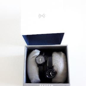 Skagen Women's SKW2364 Hagen Analog Display Analog Quartz Black Watch NYPRIS 1793,00 - jeg har kvittering. Diameter på ur kasse 20 mm Rem materiale: læder BREDDE 8 MM Super cool dobbelt dame ur fra Skagen ur. 2 ur kasser som man selv kan justerer på den sorte rem af kernelæder. Rem viklet 3 gange om håndled.   Rem bredde: 8 mm Case Størrelse: 20 mm Analog-kvarts bevægelseskasse Diameter: 20 mm Vandtæt til 165 Fod. Uret er aldrig brugt. Har original æske og kvittering.