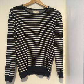Fin, mørkeblå sweater med hvide striber. Let oversize fit. Stoffet er i en kraftig kvalitet (viskose- og polyamidblanding).