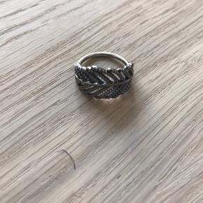 Denne ring, der er fremstillet i sterlingsølv, er forsynet med et flot udskåret fjerdesign.