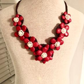 Anerledes halskæde med små røde blomster i et organisk materiale. Jeg er ikke sikker på om blomsterne er en slags nød -men noget i den stil. Der medfølger også en ring. Ring er str.52-53.  Halskæden har været brugt en gang den kan indstilles til 2 længder.