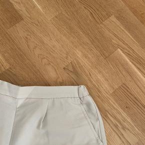 Løse shorts i kraftig kvalitet med lommer   Str: L, men passer også en M  Farve: sandfarvet / lys beige  Stand: brugt få gange