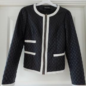 Brand: Classic Fashion Varetype: smart kort jakke Farve: Sort / hvid  Brystvidde 2 x 46 cm  Længde: 53 cm  Materiale: polyester