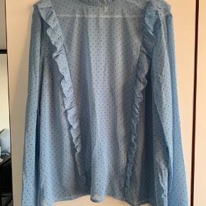 Skjortebluse i let og tyndt materiale. Er lidt gennemsigtig. Den har fine flæsedetaljer og bindes i nakken. Fejler intet!