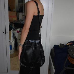 Varetype: skuldertaske læder bucket taske Størrelse: Large Farve: Sort Oprindelig købspris: 2500 kr. Prisen angivet er inklusiv forsendelse.  110 cm rem 32 høj 40 bred 100 % læder. Rummelig bucket taske i cow dvs ko læder. Tasken har en lomme på ydersiden, et rum indvendig og justerbar skulderstrop   NUL BYTTE. modellen er 176 cm og bruger selv en str small. skambud ignoreres. kan hentes i KBH K. sender også med dao til 39 kr. kun seriøse bud tak.byd ikke hvis du ikke mener det. jeg tager mobilepay på tlf :93 86 38 96 til camilla c. glæder mig til at høre fra jer:)  bemærk sælger 4 stk i alt. 500 kr pr taske. helt nye.