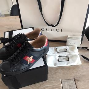 Gucci Ace sko Str. 40 De er blevet brugt maksimalt 10 gange og er blevet passet godt på, derfor er standen næsten som ny. Kasse, begge dustbags, pose og Gucci autencitet kort medfølger.  Sælger skoene for min bror, og hans mindste pris er 2500 kr - ny pris 4000 kr.  Skriv gerne for flere billeder eller eventuelle spørgsmål.