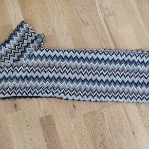 Kort tunica kjole i meget fin stof med lidt glimmer. Foret. Lynlås i ryggen. Måler 80cm i længden og ca. 44cm i bredden. Farven afhænger af hvordan lyset falder på.