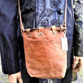 Brand: Etnisk design - ( rollespil / middelalder ) - skulder og crossbody Varetype: taske - taske fra Afrika - råt stamme look Størrelse: 22 x 21 cm Farve: natur  Syet sammen af læder / skind stykker , som ikke er stive , men ret bløde . Lukket med løbegang af skind trenser og snøre . Skulder rem , der kan reguleres . Sort stof for . Måler ca 20 x 20 cm og en bund på ca 10 x 13 cm . Skulder rem måler ca 106 cm , kan reguleres godt 12 cm .