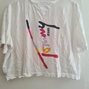 Sød Croppet T-Shirt af Mærket Tommy Hilfiger med fede detaljer.  Er brugt 2 gange, fejler intet, og kan bruges mange, mange gange endnu.  Farve: Hvid med mønster. Str: Large.  Nypris: 400 kr. Sælges for: 115 kr.