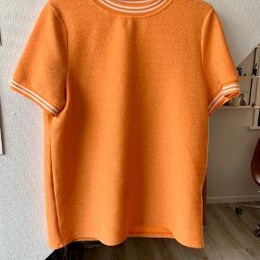 Orange glimmer trøje i str. XL Der er nogle entre fejl i stoffet som vist på billedet  den har dog kun været i brug en enkel sommer
