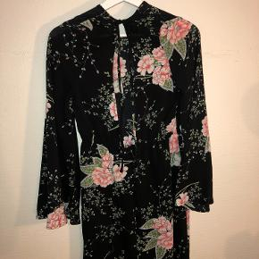 Kjole er fra Pretty Little Thing købt hos ASOS. Kjolen er blomstret og har elastik ved taljen. Den har en åben ryg og store ærmer. Kjolen er brugt, men er i god stand.