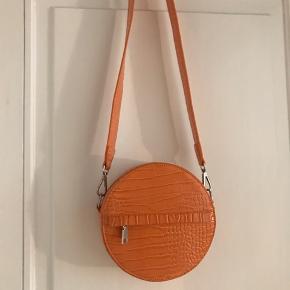 Rund taske i orange skind. Haft den på ud at handle og ellers aldrig brugt den. Fremstår som ny. Mp 200,-  Byd