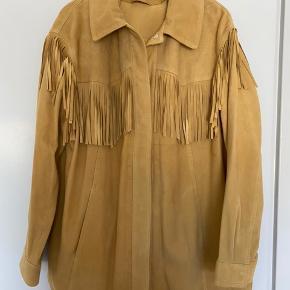 Ruskindsjakke i meget blødt skind med frynser fra H&M.   Str M, lidt oversize. Smuk lys sand/beige.   Lukkes med trykknapper. Ikke foret.