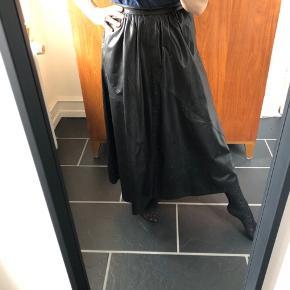 Super lækker A-formet nederdel i sort skind. Det er lommer i og lille lynlås bagpå og knap. Dansk produceret.