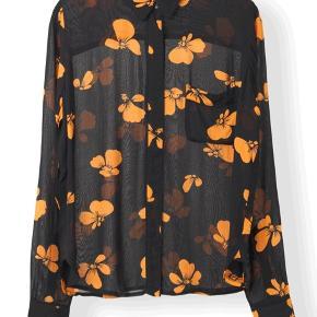 Sort skjorte fra Ganni med orange blomsterprint.