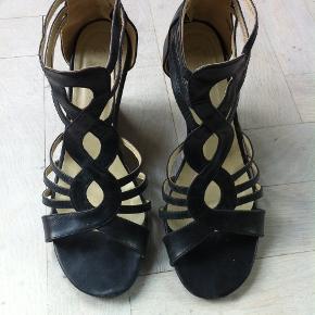 Sorte flotte sandaler i skind, med 7,5 cm høj hæl. Lukkes med lynlås bagpå.