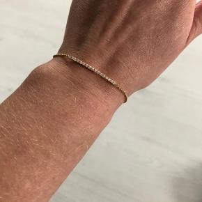 Smukt armbånd fra Julie Sandlau i forgyldt sterlingsølv med små sten. Der et to længde-indstillinger. Længde inkl. lås er enten 16 eller 18 cm afhængig af indstillingen. Aldrig brugt. Kassen har lidt skrammer foran og på bunden. Kvittering haves desværre ikke længere.