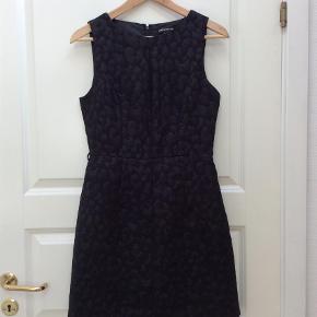 Varetype: Mini Farve: Sort  Super smuk og velsiddende kjole i flot stof med en smule metaltråd i mønsteret.