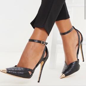 Helt nye sorte læder stiletter med guld spidstå, fra PrettyLittleThing (PLT). De er en størrelse 5 som svarer til en str.38 men synes de er ret store i størrelsen, så en str.39 er mere passende, eller en stor 38.  Kunne ikke selv passe dem, da jeg er en 37-38. En skam, for det er VIRKELIG nogle flotte elegante court heels! 12cm i højde.   Skriv gerne et bud ☺️