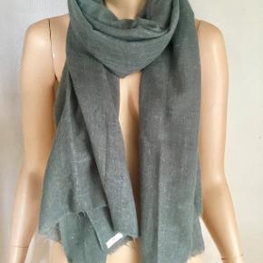 Uldtørklæde fra DAY Birger et Mikkelsen. Måler 70 cm. x 210 cm. Grå-grøn nuance. 100 % uld - blødt og lækkert. Aldrig brugt. Oprindelig købspris : 800,- Sender gerne på købers regning : DAO 39,-
