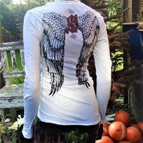 Brand: goth- sinful Varetype: bluse - bevinget Farve: Hvid  Bomulds bluse , med smukt engle vinge print . Har lidt pletter på venstre side af for stykke ; derfor billig . Måler ca 45 x 2 = 90 cm i bryst vidde . Længde er ca 67 cm og ærmer måler ca 62 cm .
