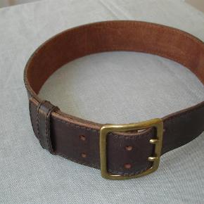 Varetype: Råt, groft mørkebrunt, bredt læderbælte med grove stikninger Størrelse: 85 X 5/5 cm Farve: Mørk brun  Rigtig sejt og groft læderbælte med grove stikninger langs kanterne i flot mørk brun med råt metalspænde i størrelse 85 cm og 5,5 cm bredt. Aldrig brugt. BYTTER IKKE!