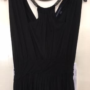 Lang sort kjole / maxikjole, som falder flot og har fine detaljer foroven. Går ind under barmen. Lynlås i ryggen.