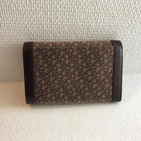 Super fin pung med det klassiske DKNY mønster. Der er plads til 10 kort, og der er en stor lynlås-lomme med to rum i. Derudover er der en stor lomme til sedler samt en lomme på bagsiden.