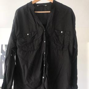 Sort løstsiddende skjorte med knapper og lommer.