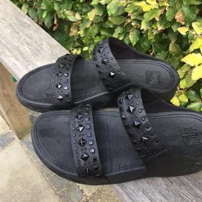 Sort Fitflop med sorte nitter/studs Sorte læderremme og læderbagkappe Kun brugt få gange da jeg har fået hallux valgus (knyst) og har brug for fodindlæg Sandalerne har ingen fejl / mangler Forsendelse DAO/ Coolrunner Betaling evt MobilePay