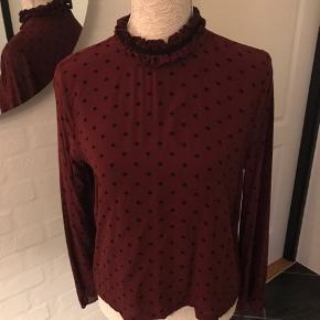 Super fin bluse fra Ganni, brugt en håndfuld gange. Fejler intet, sælges da den ikke bliver brugt.  Det er en str. L og måler 53 cm over brystet, fladt liggende. Mp 154 kr pp
