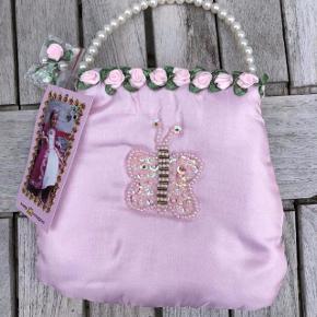NY Prinsessetaske med sommerfugl Farve: Rosa Oprindelig købspris: 200 kr.  Super fin helt NY prinsessetaske med palliet-sommerfugl, blomsterkanter og fin perlehank. Har flere hvis ønskes. Pris pr. taske 75 kr. pp