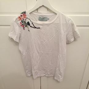T-Shirt fra Moves, str. S, blomsterbroderi på højre skulder. Kan sende med DAO, køber betaler fragt Sletter annoncen når varen er solgt