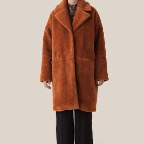 Denne frakke i er fremstillet i en faux fur-kvalitet med tekstur. Frakken har et oversize fit, stor krave, stofbetrukne trykknapper og lommer foran med skjult lynlås.  100% Polyester