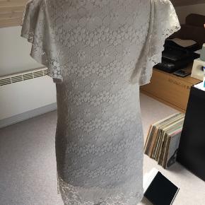 Fin sommerkjole i hvid elastisk blonde. Mærke ukendt. Str. fremgår ikke men kan passes af en S og M.  Kjolen er helt ny - kun prøvet på.