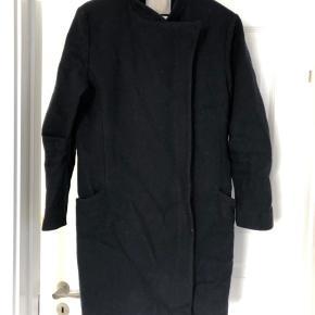 Fin uldfrakke i 78% uld. Knælænge.  Brugt, men stadig god stand. Trenger til en rens.  Kraftig sølvfarvet lynlås. Ingen fnuller på.