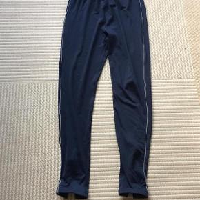 Mørkeblå træningsbuker str M med hvid stribe på benene og lynlås forneden. Snøres til i livet.