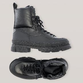 Sælger disse super fede Ganni hiking mix boots.  Utility-inspirerede boots i læder med snørelukning og super chunky, ribbet gummisål. Brug dem til et praktisk outdoorlook, eller skab et 90'er-inspireret grungelook med en kort, blomstret kjole.  Skaft til lige over anklen Komfortabel hæl på 3,5 cm Tydelig gummikant Rund tå Diskret GANNI logo bag anklen Strop bagpå Overdel i læder med gummisål og snørebånd af nylon Lavet i Portugal  Nypris 2900 ,-