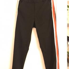 Sorte bukser med orange/hvid stribe ned af benet.  Str. M/32.