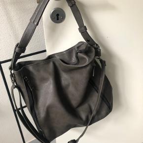 Rigtig lækker skulder - crossbody - shopper taske med både regulerbare lang rem og skulderrem.  Tasken har to fine rum på langs foran på tasken . Stort rum indeni med mindre lynlåsrum.  Kraftige lynlåse . Fed mørk grå farve  Ingen slidtage - hverken indeni eller udenpå . Stort set aldrig brugt.  Købt i Neye til 499,-  Måler 40x 37 cm og har masser af plads.  Sendes med DAO på købers regning Prisen er fast , bytter ikke.