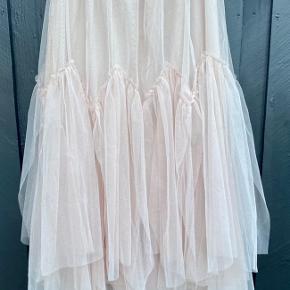 Cremefarvet lang tyl nederdel med elastik i taljen, fra Azara Paris. Da det er en kollektionsprøve, har den aldrig været brugt.