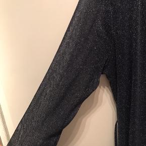 Flot glitterkjole i mørkeblå med 1/2 ærmer i gennemsigtigt stof. Flot kant, der falder på begge forstykker og hele vejen på nedre kant, Slå-om med bånd, der kan bindes for eller bag.  Brugt 2 gange, fremstår som ny.