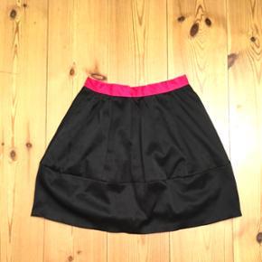 Str 34. Sort nederdel med pink kant i lidt tykt og skinnende stof. Kun brug en gang.   Se også mine andre annoncer, med gode priser på blandt andet tøj fra designers remix, Won Hundred og mbyM.