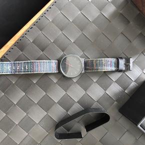 Sælger dette ur fra komono. Uret har sort skive og Urkasse, mens remmen er mørke blå (mørk jeans) med farve striber. Urboksen til opbevaring er holdbar og lavet i god kvalitet.  Uret er brugt flere gange, og det kan ses på remmen. Der er få brugstegn. Selve urkassen inkl. Glas står rigtig skarpt og er i fin stand.  Condition (rem): 4/10 Condition (Skive + glas): 8/10  Nypris: 450 kr.  Urboksen medfølger naturligvis i prisen.  Kan afhentes i holstebro eller sendes for ca. 37 kr.