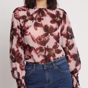 Smuk bluse i skønne farver fra YAS. Dahlia top med botanisk print på en let og transparent kvalitet. Blusen har lange ærmer med smock elastikkant nederst. Den er i fast chiffon af recycled polyester og lukkes med en lynlås i nakken. Den feminine bluse kan styles enkelt til en denim nederdel eller sættes sammen med en buks i samme farver, for et mere friskt look.