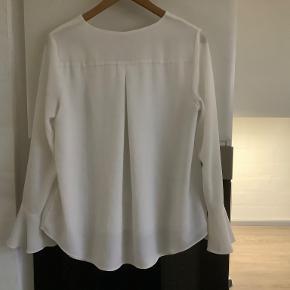 Blusen er som ny, men som det ses på sidste billede, så har den en lille brun plet/mærke på højre albue. Derfor den billige pris.