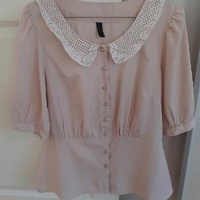 Lyserød skjorte med blonder krave.